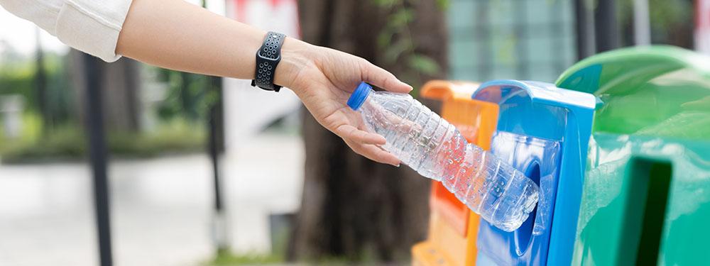 Photo d'une femme en train de mettre une bouteille dans les colonnes de tri