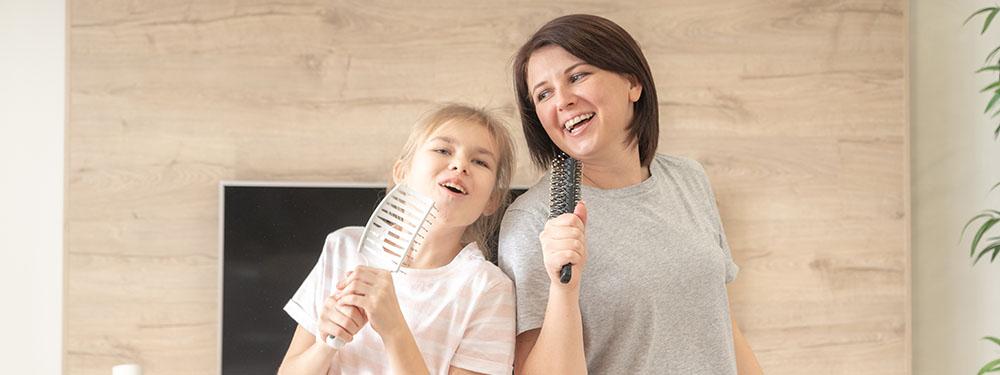 Photo d'une mère et de sa fille en train de chanter avec des brosses en guise de micros