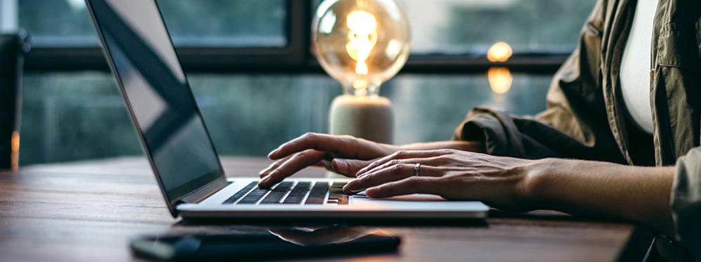 Photo d'une femme en train de taper l'écran de son ordinateur