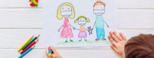 Photo montrant un enfant en train de dessiner une famille portant des masques