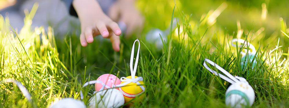 Photo d'un enfant en train de ramasser des œufs en chocolat dans son jardin