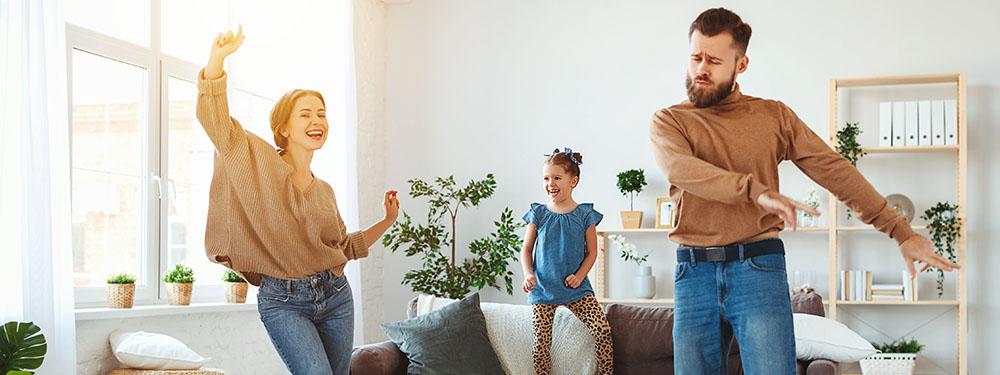 Photo d'une famille en train de danser dans leur salon