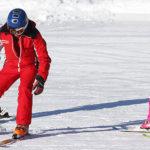 Photo d'une moniteur de ski en train de faire une leçon a des petits élèves