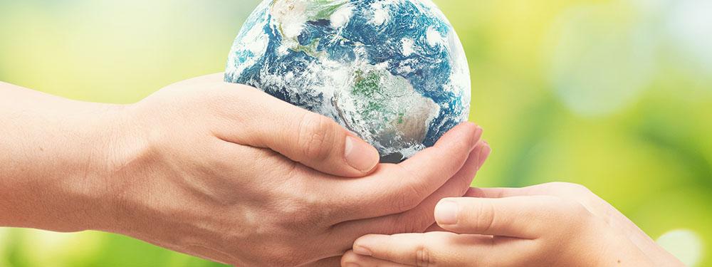 Photo d'un homme tenant dans ses mains la terre en train de le donner à des mains d'enfants
