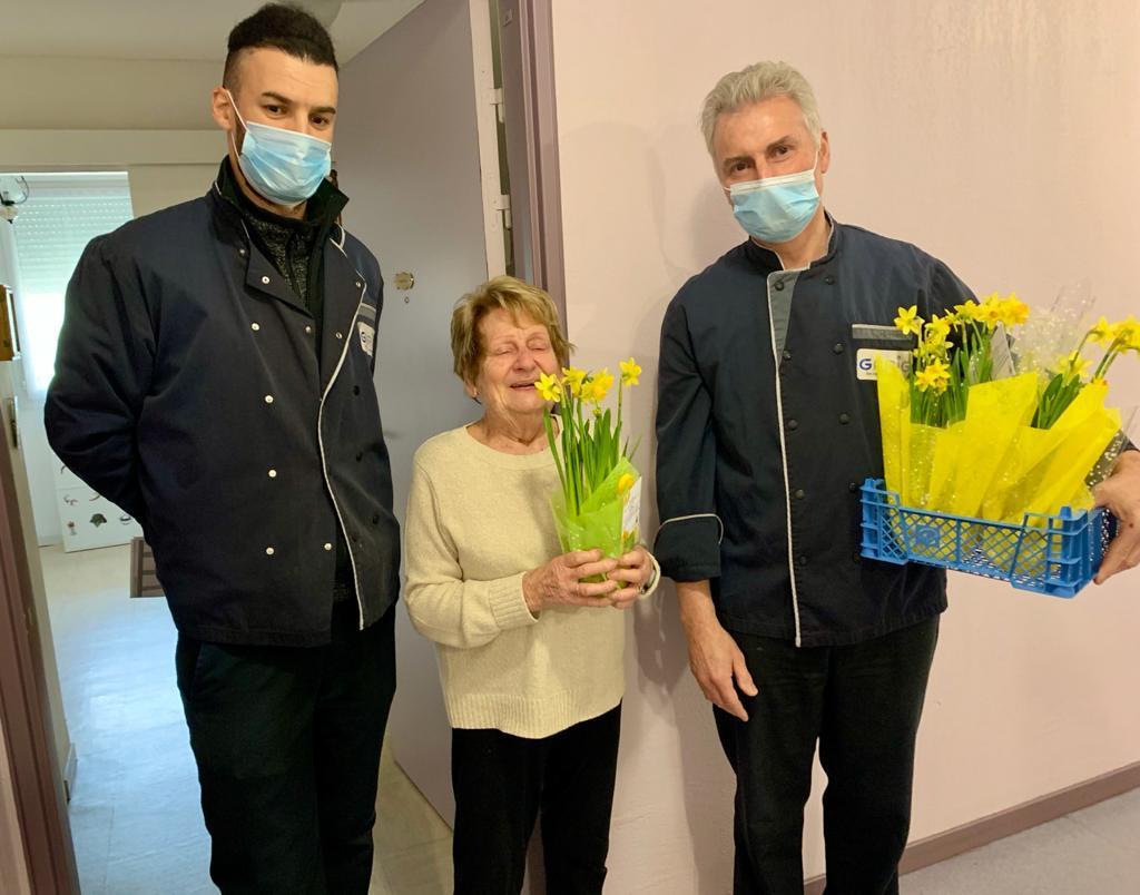 Photo montrant l'equipe de portage des repas offrant des fleurs pour la fête des grands-mères