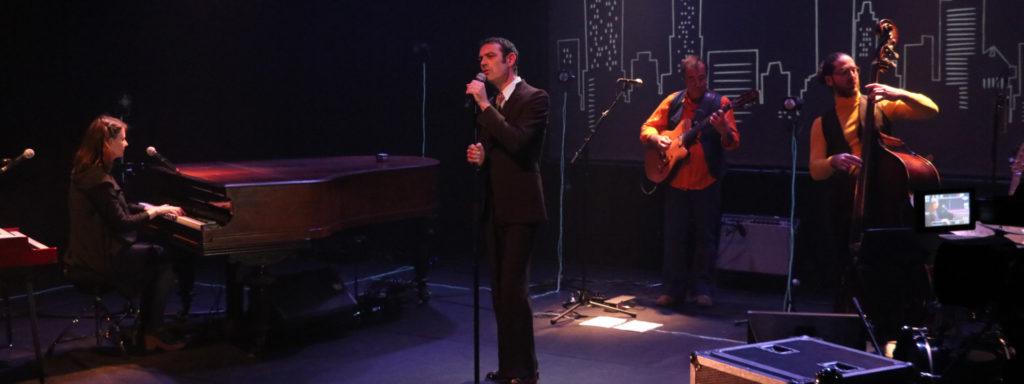 Photo représentant des artistes sur scène. Au centre de la scène on aperçoit un homme en costume cravate en train de chanter. À sa droite un bassiste et un contrebassiste. à gauche une pianiste en train de jouer