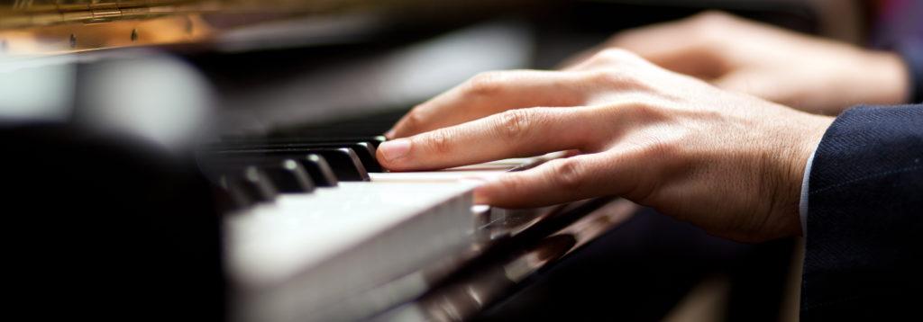 Photo représentant un pianiste en train de jouer. On voit ses mains en gros plan