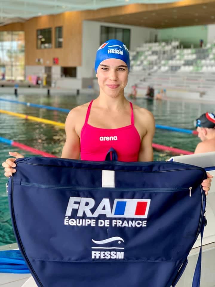 Photo d'Oriane Robisson posant devant une piscine avec un sac de l'équipe de France