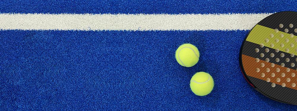 Photo d'un terrain de padel avec une raquette et des balles posés au sol
