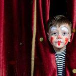 Photo d'un enfant maquillé en clown caché derrière un rideau de théâtre