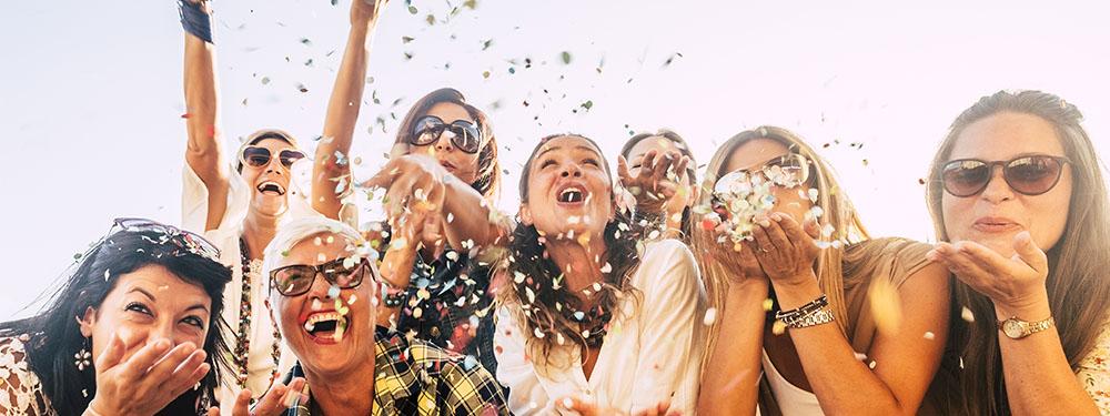 Photo montrant des femmes en train de souffler sur des confettis