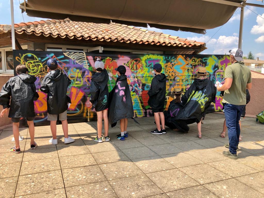 Photo de l'atelier Graff de la médiathèque montrant des enfants en train de peindre à la bombe