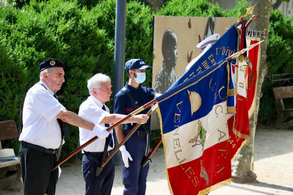 Photo de la commémoration du 18 juin montrant les portes drapeaux en pleine action