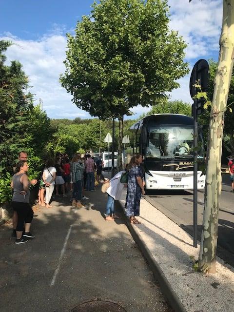 Photo du départ du séjour jeunesse montrant des parents devant le bus au moment du départ