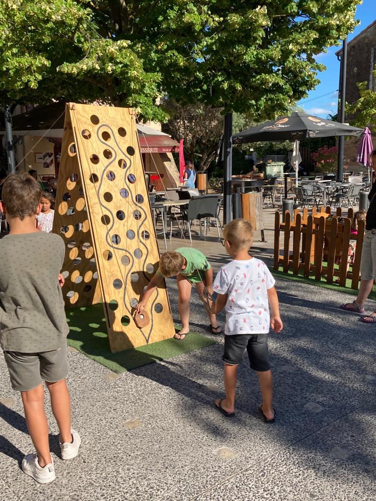 Photo montrant des enfants en train de jouer sur des jouer en bois sur la place des Logis