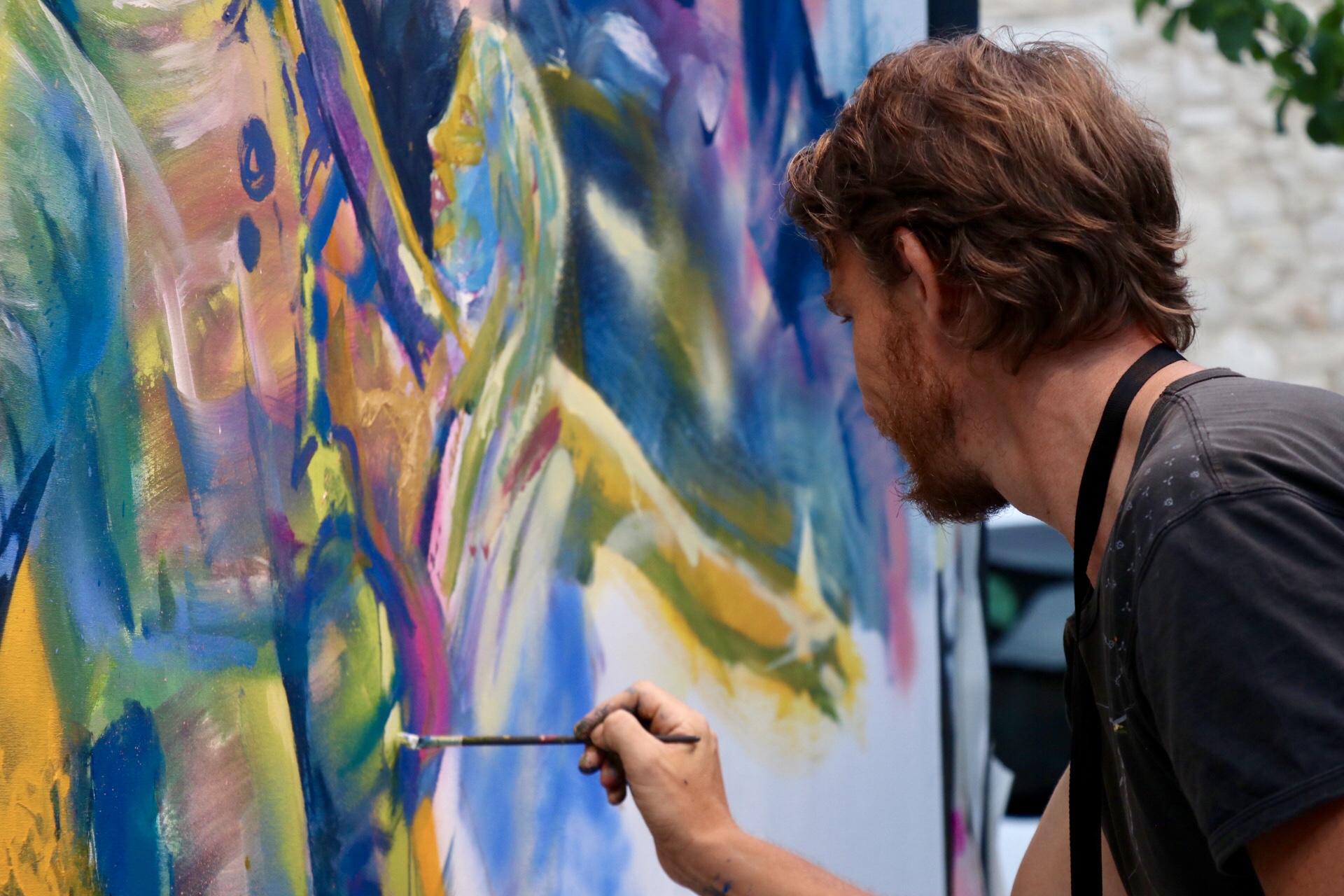 photo d'un artiste en train de peindre en live-painting pendant le street nécessaire