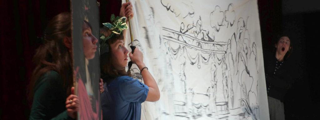 Photo représentant trois femmes sur une scène de théâtre. La première à gauche passe son visage dans un passe-tête, la seconde fait apparaître un dessin et la troisième située à droite apparaît stupéfaite bouche bée