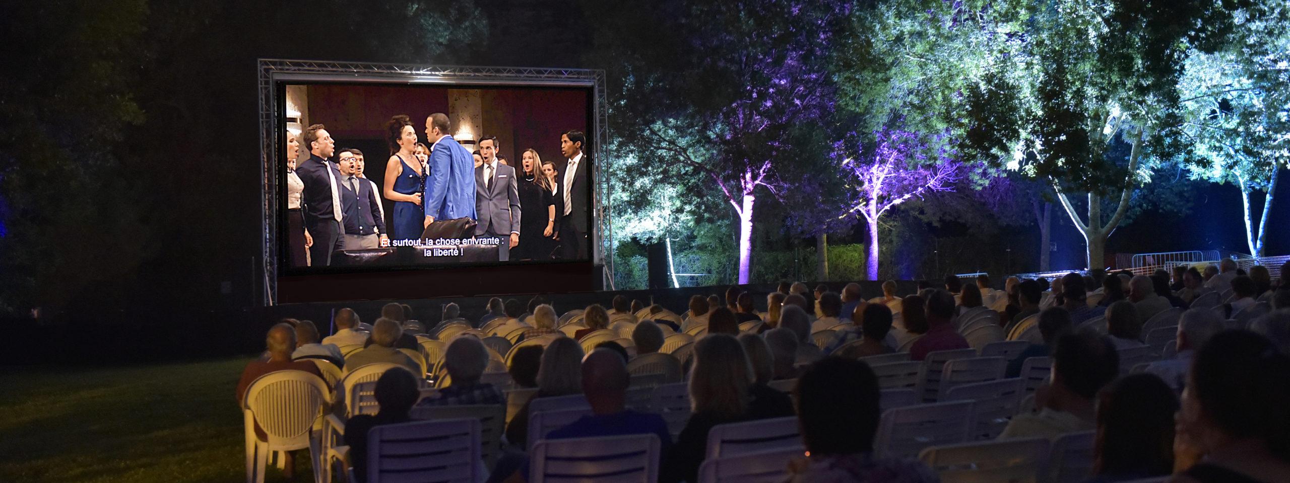 Photo représentant des spectateurs assis en plein air en train de regarder la projection d'un opéra sur grand écran